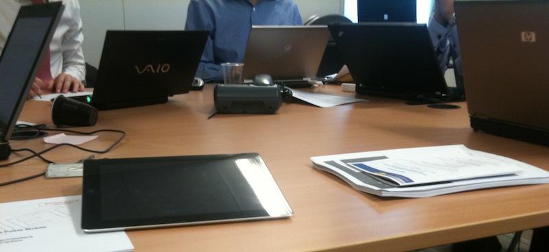 Prise de note avec un iPad en réunion au milieu d'une forêt d'écrans